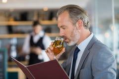 Geschäftsmann, der Bier isst und Menü betrachtet stockbilder