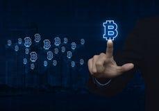 Geschäftsmann, der bitcoin Ikone mit hellblauem Weltkarteanschl. bedrängt Stockfotografie