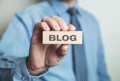 Geschäftsmann, der Blogwort im Holzklotz zeigt Lizenzfreie Stockfotos