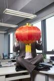 Geschäftsmann, der chinesische Laterne vor Gesicht hält Stockbild