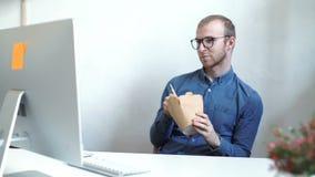 Geschäftsmann, der chinesisches Lebensmittel beim Haben eines Internet-Anrufs isst stock footage