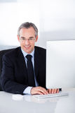 Geschäftsmann, der an Computer arbeitet Lizenzfreie Stockbilder