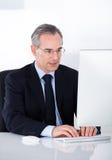 Geschäftsmann, der an Computer arbeitet Stockfotos