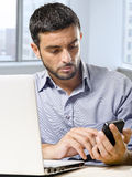 Geschäftsmann, der an Computerlaptop unter Verwendung des Handys am Schreibtisch vor Wolkenkratzerfenster arbeitet Stockfotos
