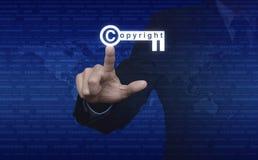 Geschäftsmann, der Copyrightschlüsselikone über digital erzeugter Weltkarte a bedrängt Stockfoto