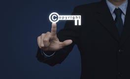 Geschäftsmann, der Copyrightschlüsselikone auf blauem Hintergrund, Kopie bedrängt Stockfotos