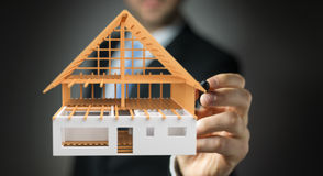 Geschäftsmann, Der 3D überträgt Unfertiges Planhaus Mit Einem PET Zeichnet  Lizenzfreies Stockbild