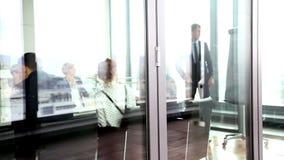 Geschäftsmann, der Darstellung unter Verwendung des flipchart hinter Glaswand gibt stock footage