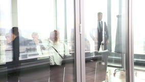 Geschäftsmann, der Darstellung unter Verwendung des flipchart hinter Glaswand gibt stock video footage