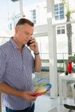 Geschäftsmann, der das Farbmuster spricht am Handy hält Lizenzfreie Stockfotografie