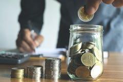 Geschäftsmann, der das Geld in das Glasgefäß für die Rettung, finanziell einsetzt Lizenzfreies Stockbild