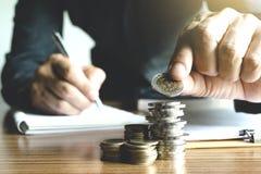 Geschäftsmann, der das Geld in das Glasgefäß für die Rettung, finanziell einsetzt Stockbilder