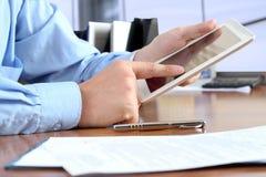 Geschäftsmann, der das Geschäft, sitzend an seinem Schreibtisch im Büro tätigt, Stockfotografie