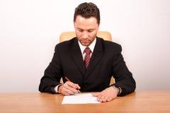 Geschäftsmann, der das Papier unterzeichnet Stockfotos