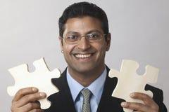 Geschäftsmann, der das Puzzlespiel zusammenfügt Lizenzfreies Stockbild