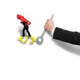 Geschäftsmann, der das rote Pfeilzeichen balanciert auf Gelduhr Han trägt Stockfoto