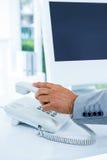 Geschäftsmann, der das Telefon beantwortet Lizenzfreies Stockbild