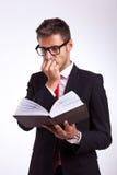 Geschäftsmann, der das Thrillerbuch liest Stockfoto