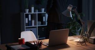 Geschäftsmann, der Datei auf Regal hält und zum Schreibtisch zurückkommt stock footage