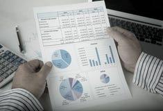 Geschäftsmann, der Datenbericht analysiert stockbild