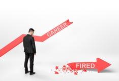 Geschäftsmann, der defekten Pfeil mit u. x27 betrachtet; fired& x27; Wort Stockfoto
