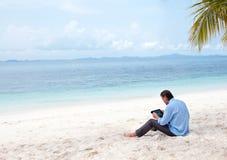 Geschäftsmann, der an dem Strand mit Ipad arbeitet