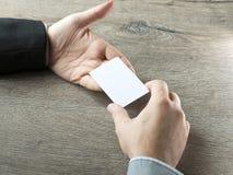 Geschäftsmann, der dem Teilhaber mit Holztischhintergrund Visitenkarte gibt Lizenzfreie Stockfotografie