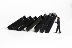 Geschäftsmann, der den Domino-Effekt stoppt lizenzfreie stockfotos