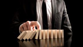 Geschäftsmann, der den Domino-Effekt stoppt Stockfoto