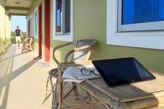 Geschäftsmann, der in den Hintergrund mit Gläsern, Zeitung und Laptop auf Holztisch im Motelbalkon geht Stockfotos