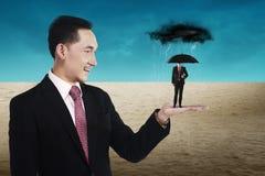Geschäftsmann, der den kleinen Mann verwendet Regenschirm hält Stockfotografie