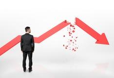 Geschäftsmann, der den roten gebrochenen Pfeil des fallenden Diagramms lokalisiert auf weißem Hintergrund betrachtet Stockbilder