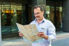 Geschäftsmann, der den Stadtführer erforscht Stockfotografie