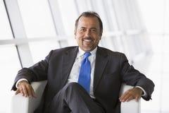 Geschäftsmann, der in der Bürovorhalle sitzt Stockfoto
