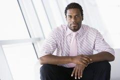 Geschäftsmann, der in der Bürovorhalle sitzt Stockbilder