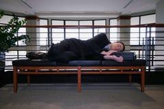 Geschäftsmann, der in der Halle schläft Stockfotografie