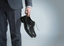 Geschäftsmann, der in der Hand die Schuhe anhält, Lizenzfreies Stockbild