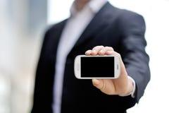 Geschäftsmann, der in der Hand intelligentes Mobiltelefon hält lizenzfreies stockbild