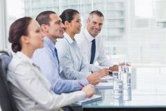 Geschäftsmann, der an der Kamera während sein Kollegehören lächelt Stockfotografie