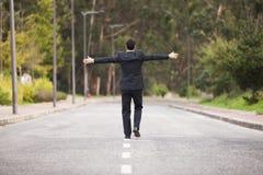 Geschäftsmann, der an der Straße geht Lizenzfreie Stockfotos