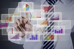 Geschäftsmann, der Diagramm auf Geschäftsschnittstelle wählt Stockfotografie