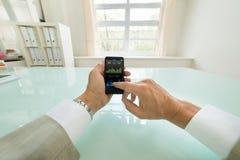 Geschäftsmann, der Diagramm auf Mobiltelefon analysiert Stockbild