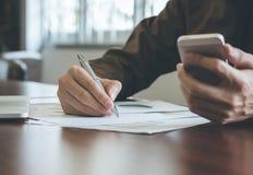 Geschäftsmann, der Diagrammdokument mit Laptop analysiert und Handy im Büroweinleseton verwendet Lizenzfreies Stockbild