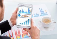 Geschäftsmann, der Diagramme auf digitaler Tablette am Schreibtisch vergleicht Stockbilder