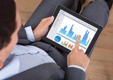 Geschäftsmann, der Diagramme auf digitaler Tablette vergleicht Stockfotografie