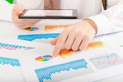 Geschäftsmann, der Diagramme und Diagramme analysiert Stockfotografie