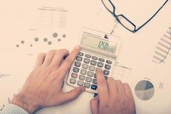 Geschäftsmann, der Diagramme und Statistiken überprüft lizenzfreie stockbilder