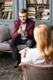 Geschäftsmann, der die dunkelrote Jacke teilt seine Sorgen mit Therapeuten trägt lizenzfreies stockfoto