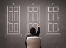 Geschäftsmann, der die rechte Tür wählt Lizenzfreie Stockbilder