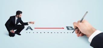 Geschäftsmann, der die rote Linie von a zu b eigenhändig gezeichnet betrachtet Stockbilder